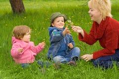 Divertimento della famiglia nell'erba Fotografia Stock