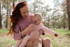 Divertimento della mamma che gioca con sua figlia un il pezzo di ramoscello nel parco Fotografia Stock