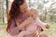 Divertimento della mamma che gioca con sua figlia un il pezzo di ramoscello nel parco Immagine Stock