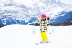 Divertimento della neve e dello sci Bambino in montagne di inverno Immagine Stock Libera da Diritti