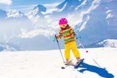 Divertimento della neve e dello sci Bambino in montagne di inverno Immagini Stock Libere da Diritti