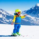 Divertimento della neve e dello sci per il bambino in montagne di inverno Fotografie Stock