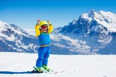 Divertimento della neve e dello sci per il bambino in montagne di inverno Immagine Stock