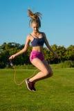Divertimento della ragazza che salta sulla corda di salto con un sorriso Fotografia Stock