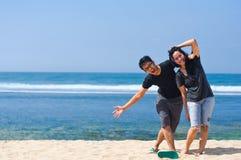 Divertimento delle coppie alla spiaggia Immagine Stock