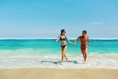 Divertimento delle coppie sulla spiaggia Gente romantica nel funzionamento di amore in mare immagine stock libera da diritti