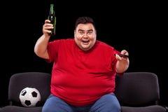 Divertimento di calcio - felice ed uomo grasso che guarda TV, prendendo birra e pallone da calcio su fondo nero Fotografia Stock
