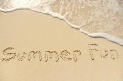 Divertimento di estate scritto in sabbia sulla spiaggia Fotografia Stock