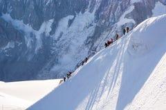 Divertimento di inverno in alpi - scendendo il pendio Fotografie Stock Libere da Diritti