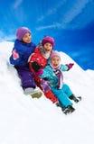 Divertimento di inverno, bambini felici che sledding all'orario invernale Fotografie Stock