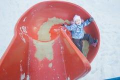 Divertimento di inverno della bambina sullo scorrevole di plastica rosso del campo da giuoco fotografia stock