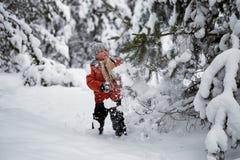 Divertimento di inverno il ragazzo da solo vaga attraverso la foresta nevosa dell'inverno Fotografia Stock Libera da Diritti