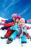 Divertimento di inverno, neve, bambini che sledding all'orario invernale Fotografia Stock Libera da Diritti
