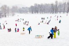 Divertimento di inverno, neve, famiglia che sledding all'orario invernale Immagine Stock Libera da Diritti