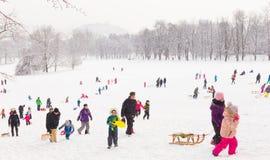 Divertimento di inverno, neve, famiglia che sledding all'orario invernale Immagini Stock Libere da Diritti