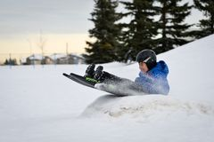 Divertimento di inverno - Sledding/Tobogganing del bambino velocemente sopra la rampa della neve fotografia stock libera da diritti
