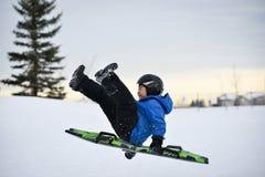 Divertimento di inverno - Sledding/Tobogganing del bambino velocemente sopra la rampa della neve Fotografia Stock