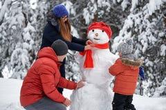 Divertimento di inverno una ragazza, un uomo e un ragazzo facenti un pupazzo di neve fotografia stock