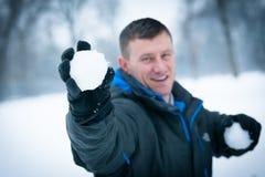 Divertimento di inverno: Uomo nella lotta della palla di neve Fotografia Stock Libera da Diritti