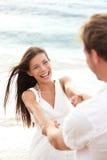 Divertimento di vacanze estive della spiaggia con le coppie allegre Fotografia Stock