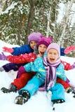 Divertimento do inverno, crianças felizes que sledding no tempo de inverno Imagens de Stock Royalty Free