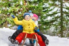 Divertimento do inverno das crianças no pequeno trenó que desliza para baixo Foto de Stock Royalty Free