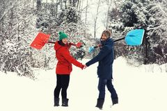 Divertimento do inverno: pares felizes com pás da neve Imagem de Stock