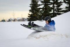 Divertimento do inverno - Sledding da criança/Tobogganing rapidamente sobre a rampa da neve Foto de Stock Royalty Free