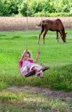 Divertimento do verão, menina em um balanço de madeira