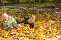 Divertimento e giochi con i fogli di autunno fotografia stock libera da diritti