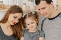 Divertimento e una bella famiglia di tre divertendosi nella cucina fotografie stock