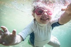 Divertimento feliz da criança da criança que nada debaixo d'água durante férias dos feriados da praia do verão fotografia de stock royalty free