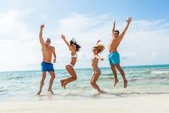 Divertimento feliz novo do havin dos amigos na praia imagem de stock