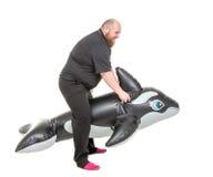 Divertimento gordo do homem que salta em um golfinho inflável Fotografia de Stock