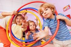 Divertimento nel ragazzo attivo e nelle ragazze di lezione della classe con il cerchio fotografia stock