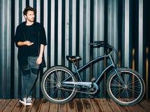 Divertimento Retrato da noite com um flash de um homem novo em um equipamento preto elegante e nas sapatilhas que levantam com um Imagem de Stock