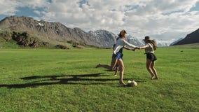 Divertiresi d'avanguardia delle ragazze dei pantaloni a vita bassa all'aperto Tre donne sveglie stanno girando su erba verde Migl archivi video
