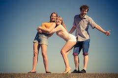 Divertiresi delle ragazze del ragazzo due degli amici del gruppo all'aperto Fotografie Stock