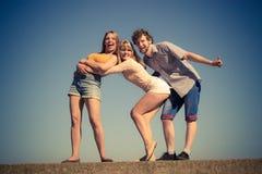 Divertiresi delle ragazze del ragazzo due degli amici del gruppo all'aperto Fotografia Stock
