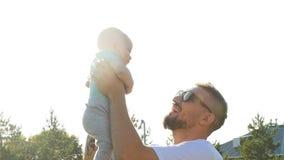 Divertiresi felice del padre getta su nel bambino al tramonto, la famiglia, il viaggio, la vacanza, il giorno del ` s del padre - stock footage
