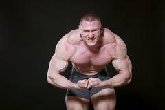 Diviértase al atleta que el culturista muestra apagado sus músculos Fotografía de archivo