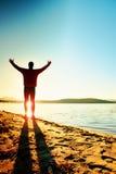 Diviértase al hombre activo que corre y que ejercita en la playa en la puesta del sol imagenes de archivo