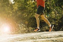 Diviértase al hombre con las piernas atléticas y musculares rasgadas que corren cuesta abajo del camino en entrenamiento del entr foto de archivo