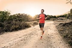 Diviértase al hombre con las piernas atléticas y musculares rasgadas que corren cuesta abajo del camino en entrenamiento del entr fotos de archivo libres de regalías