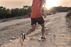 Diviértase al hombre con las piernas atléticas y musculares rasgadas que corren cuesta arriba del camino en entrenamiento del ent fotos de archivo