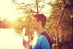 Diviértase al hombre con una botella de agua en un parque de la ciudad imagenes de archivo
