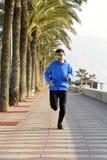 Diviértase al hombre que corre a lo largo del bulevar de las palmeras de la playa en la sesión de formación de la sacudida de la  Imagen de archivo libre de regalías