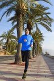 Diviértase al hombre que corre a lo largo del bulevar de las palmeras de la playa en la sesión de formación de la sacudida de la  Fotografía de archivo