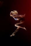 Diviértase, chica joven delgada con el cuerpo muscular hace un salto Imagen de archivo