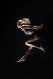 Diviértase, chica joven delgada con el cuerpo muscular hace un salto en un bla Imagen de archivo